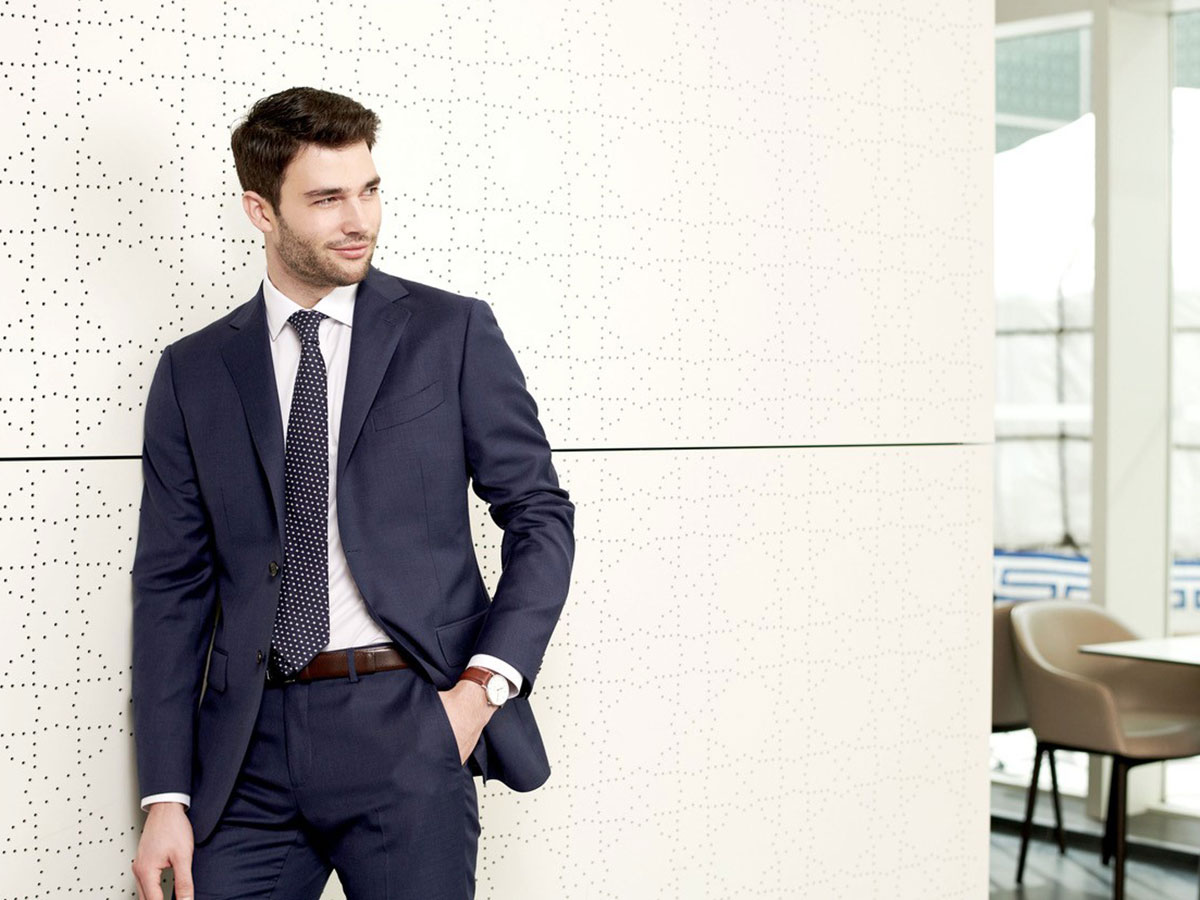 male model wearing dark blue business suit while standing by wall