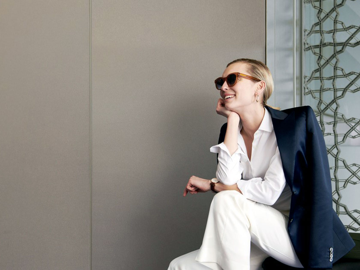 female model wearing white business suit and dark jacket while wearing sunglasses