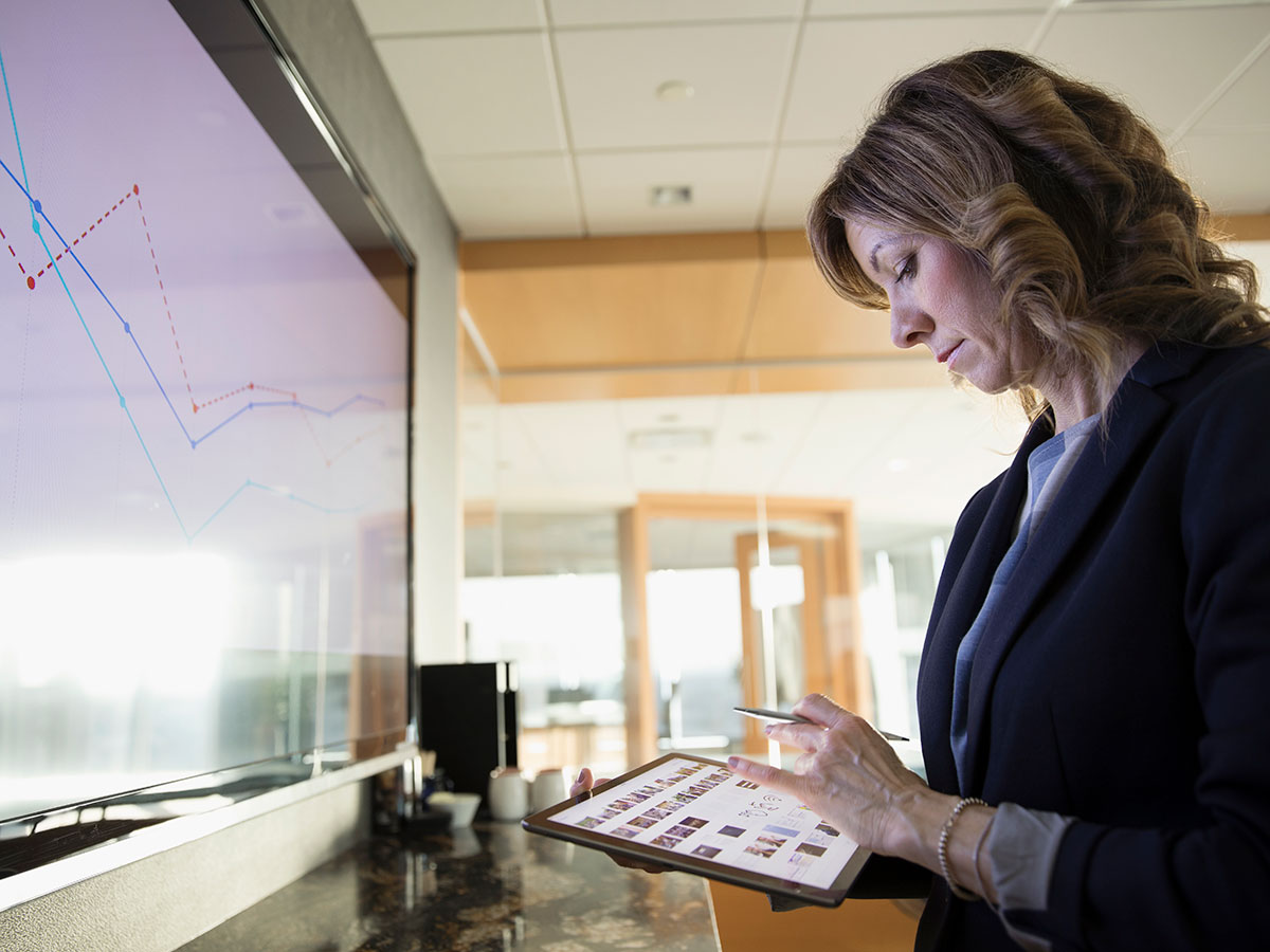 business woman using tablet while facing a presentation screen in meeting room