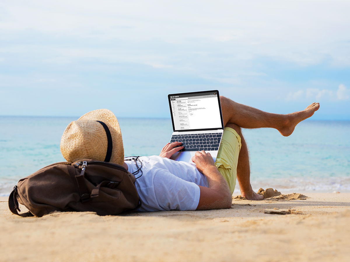 young man relaxing on beach, while reading emails on laptop