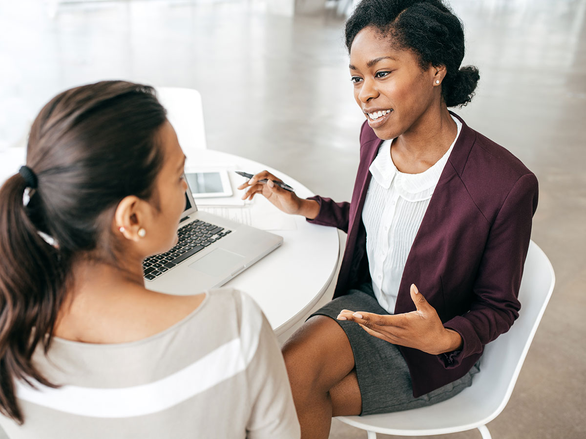 young business woman consulting another woman at a small table in an office environment