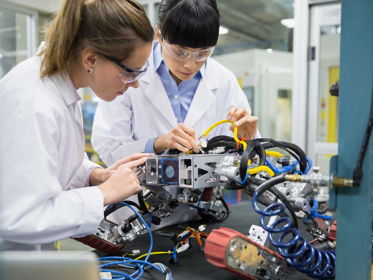 Engineers assembling robotics in factory