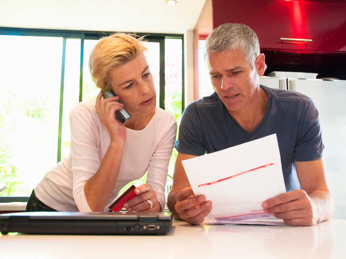 Couple looking at bill, holding credit card and talking on phone
