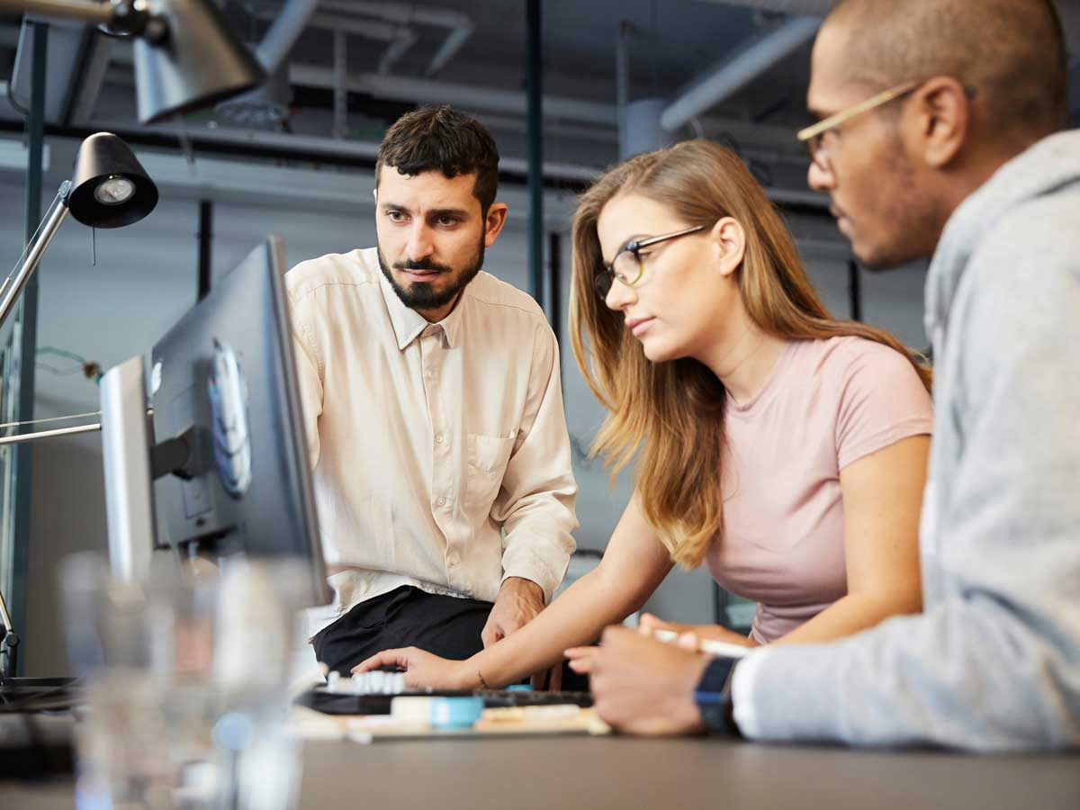 Creative male and female entrepreneurs looking at computer monitor during meeting in office