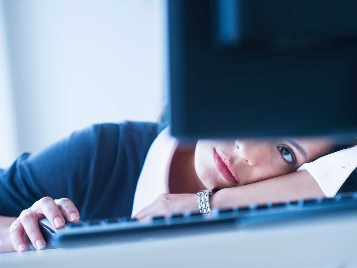 Businesswoman looking tired in front of computer