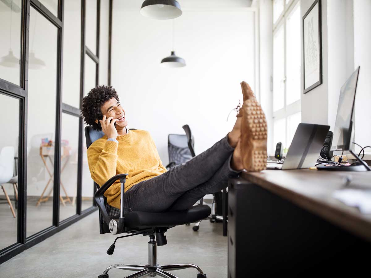 Relaxed businessman talking on phone in office with feet up on desk