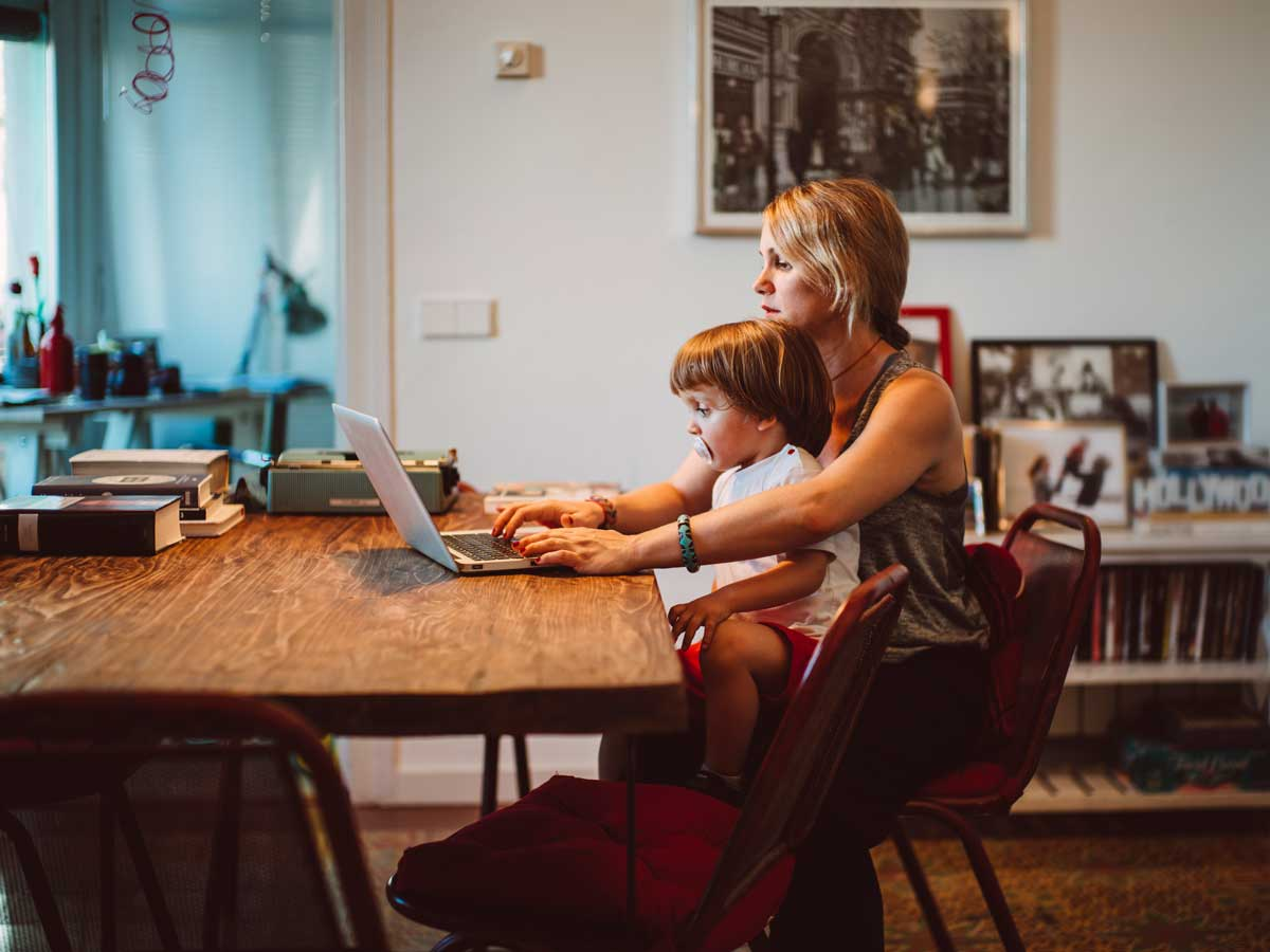 Young pregnant woman working from home while older child plays at her side