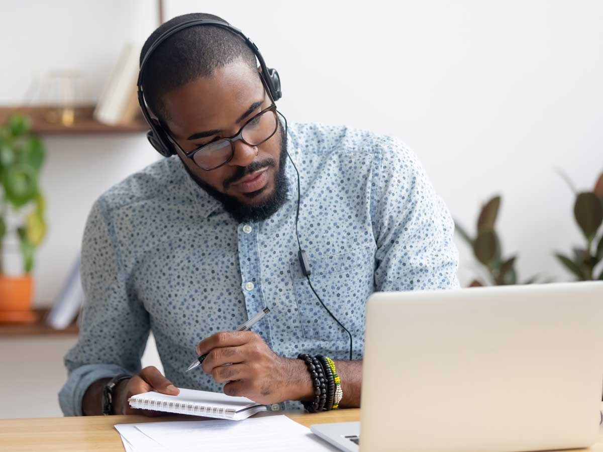 Focused businessman in headphones writing notes watching webinar