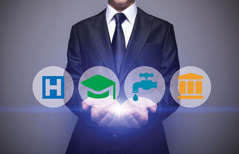 Man in suit holding hands out with light shining up from his hands to four icons for home, education, utilities and finance.