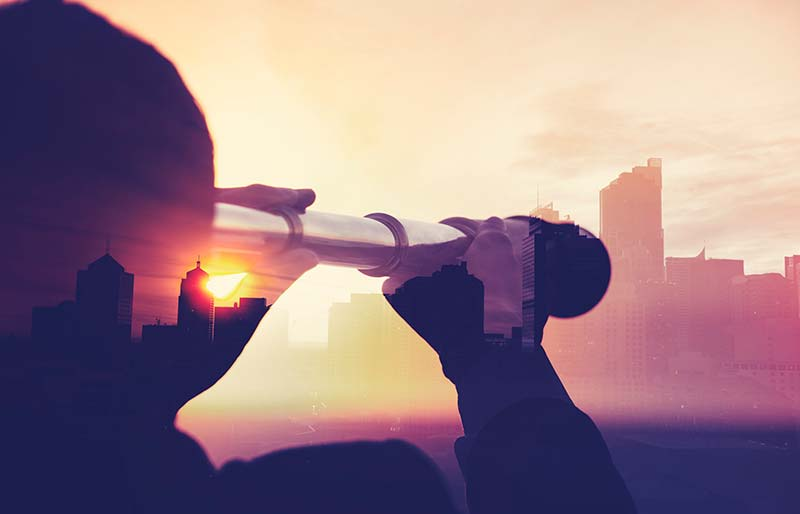 A silhouette of a business man looking at the city through a telescope during sunset.
