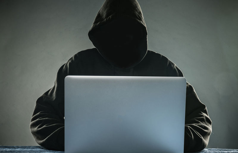 A close-up of a person in a hooded sweat shirt on a laptop, face in the shadows.