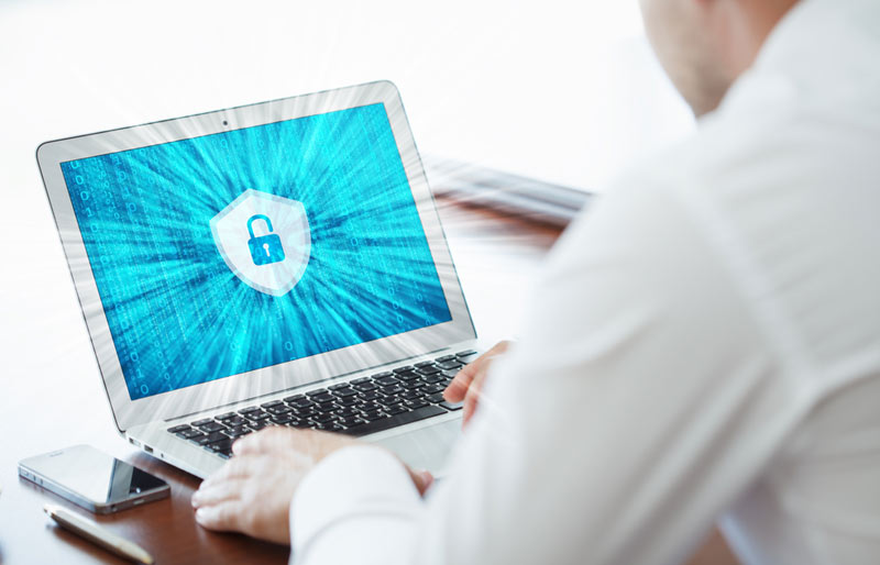 A close-up of a business professional typing on a laptop with a stylized blue padlock on the screen.
