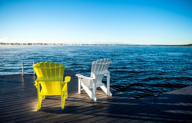 A photograph of two Muskoka chairs sitting on a deck looking out over a beautiful lake.