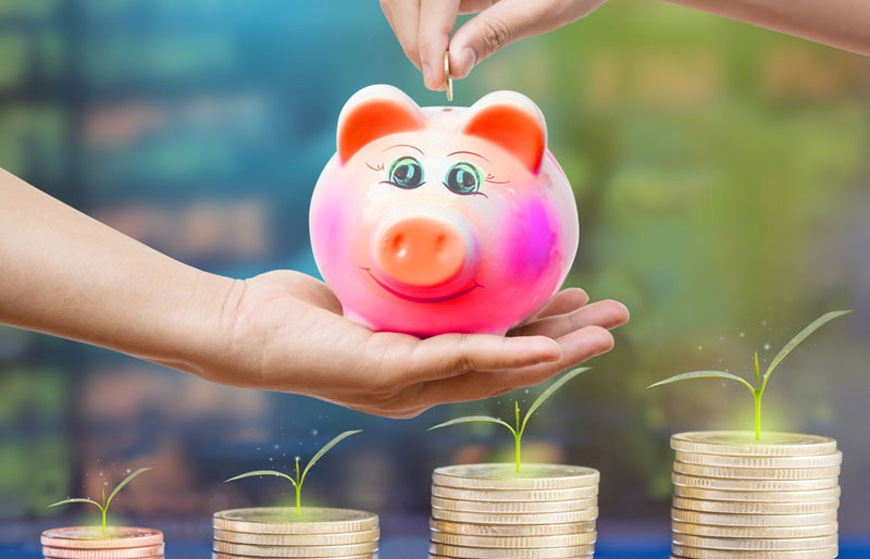 A close-up photograph of a parent holding a colourful piggy bank with a child depositing money.