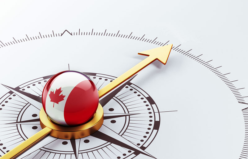 A compass pointing north with a ball with an image of the Canadian flag in the middle.