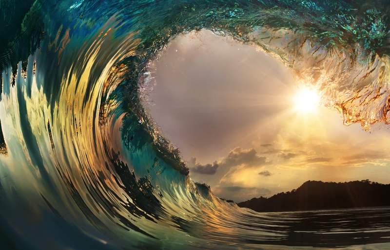 ocean surfing wave at sunset
