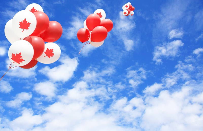 red and white Canadian balloons floating up towards the sky