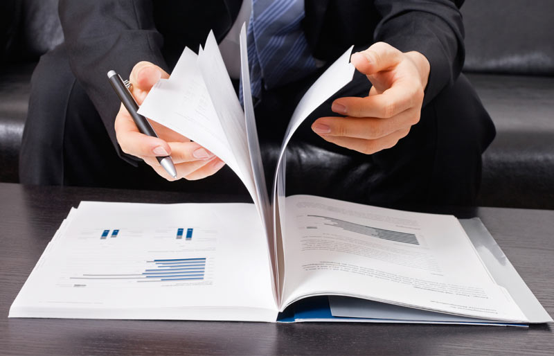 Close up of pages of a business document being flipped through by a business man in a suit.