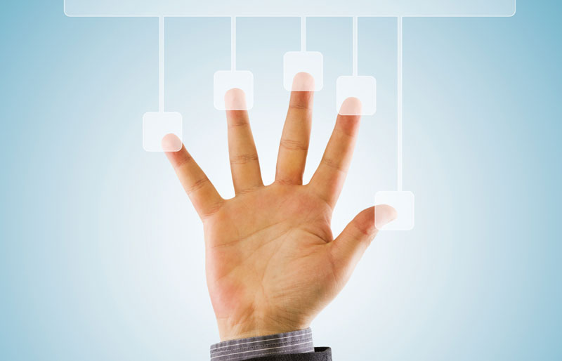 A businessman's hand is held up against a display screen, with fingers spread out to touch graphics.