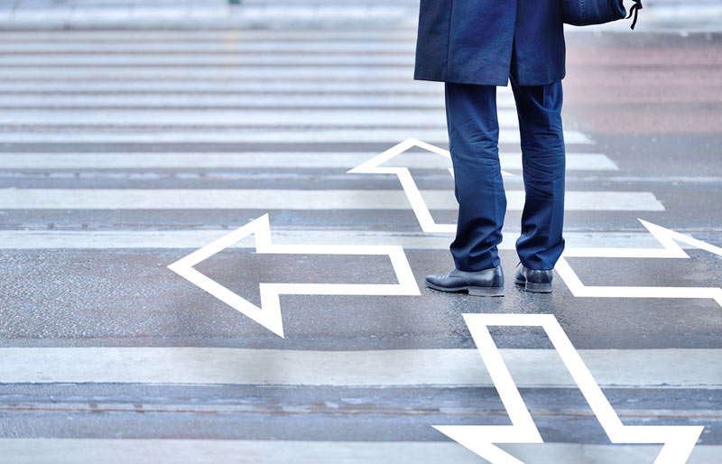 Man standing in crosswalk with four arrows pointing four different ways