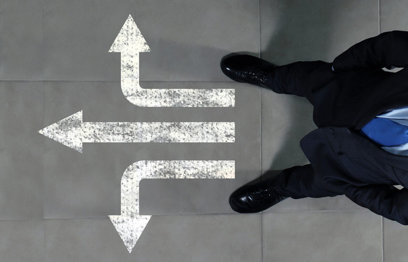 A birds-eye view of a business man standing, with three arrows that point straight, left and right, show on the tiled floor beneath him.