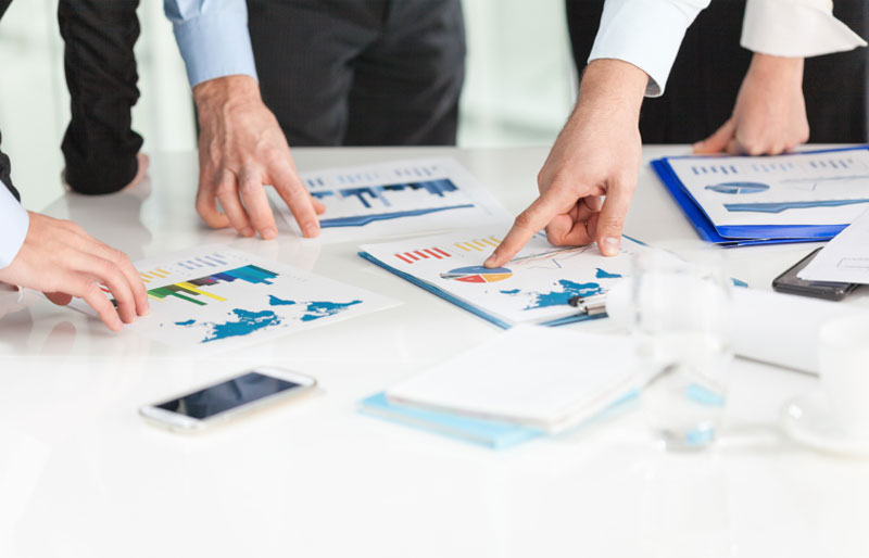 Business people pointing to financial charts on table