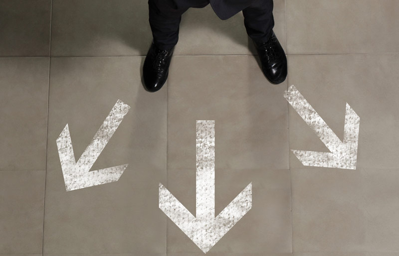 Top view of a businessman standing on a tile floor. In front of him are painted three white arrows indicating different directions, but all are forward.