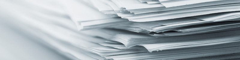 A close-up of an untidy stack of white papers as seen from one corner.