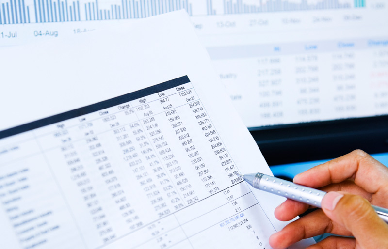 A businessman holds a pen to a spreadsheet printout.