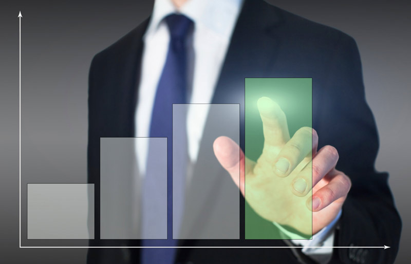 A businessman dressed in a black suit stands in front of a touch screen that displays a bar graph, his finger touches one bar that turns green.