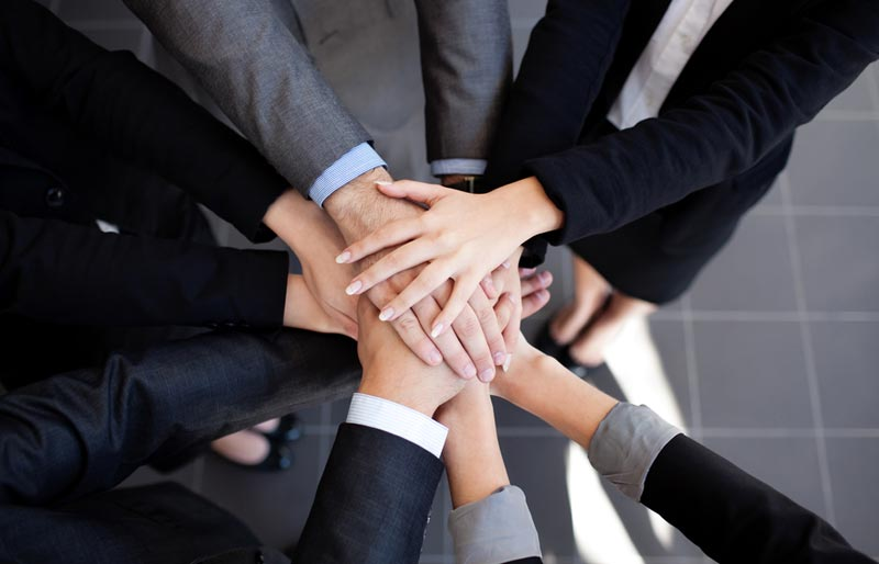 An aerial photo shows businesspeople standing in a circle with their arms reaching in towards the middle of the circle and hands stacked on top of each other.