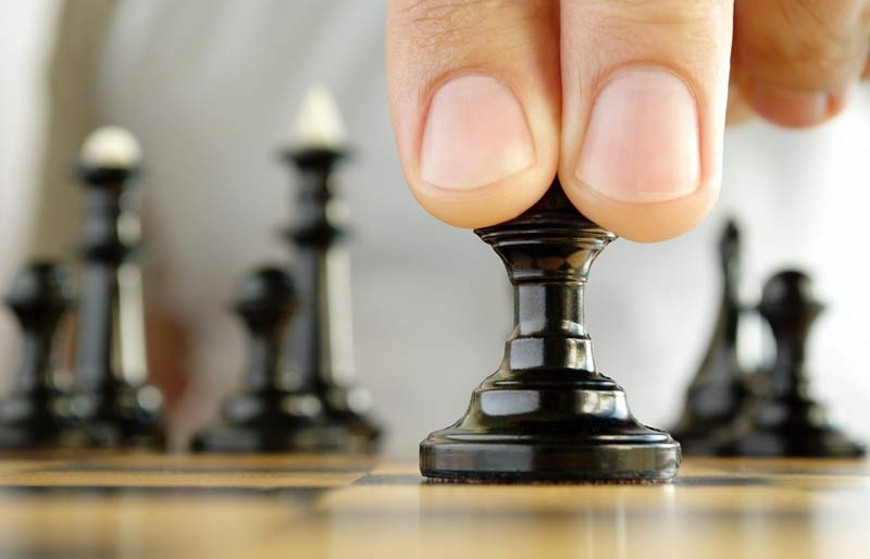 A close-up view of two fingers on a black chess piece.