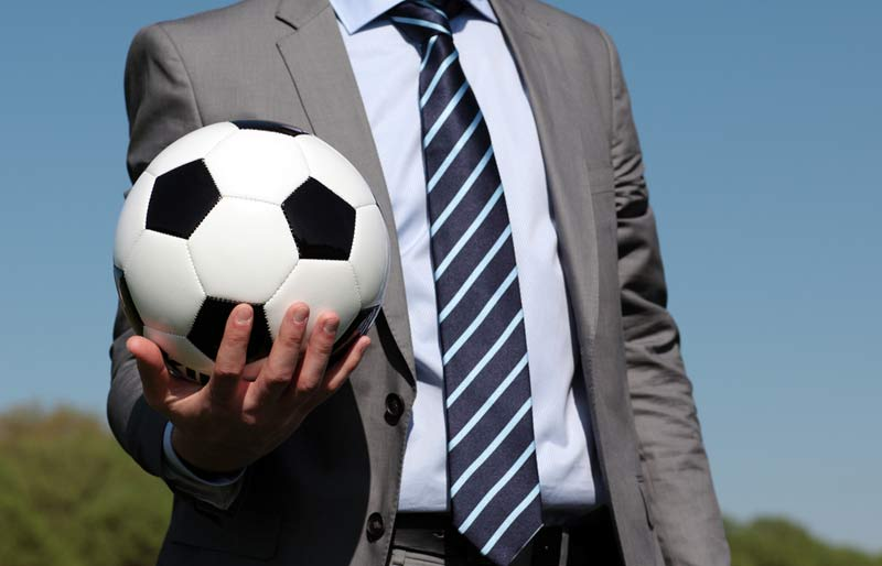 A man wearing a suit stands outdoors in front of a grassy hill set against a blue sky and holds a soccer ball in his right hand.