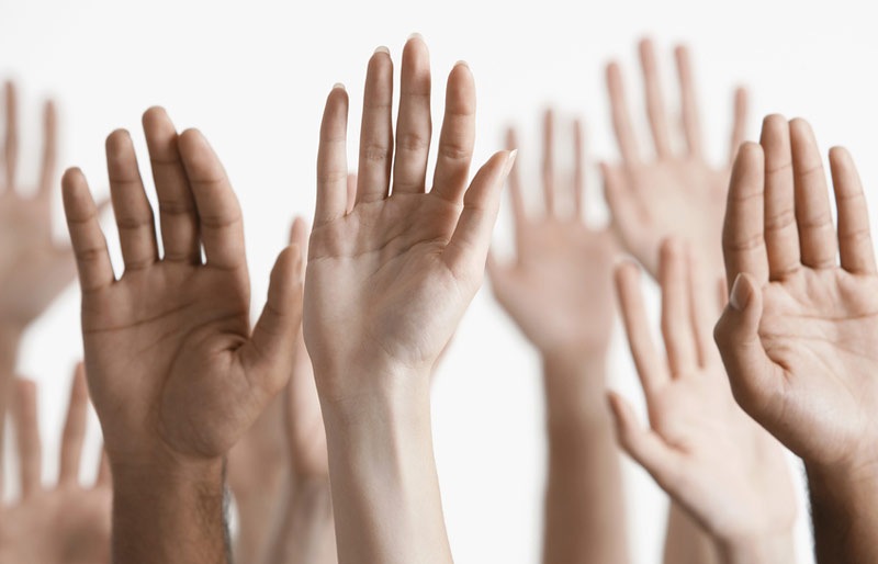 Many hands being raised as if ready to ask or answer a question.