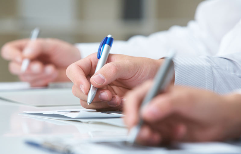 Three hands, arms clad in white shirt sleeves, are writing with pens on papers.