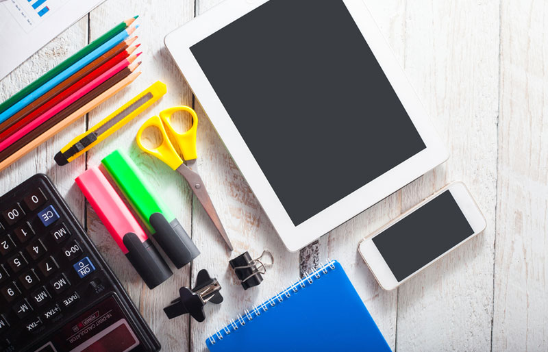 A close-up of a desk with school supplies and a tablet PC.