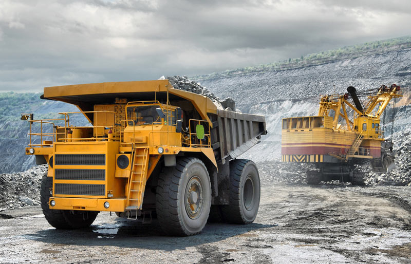 A large yellow dump truck and an excavator work in an open pit mine.