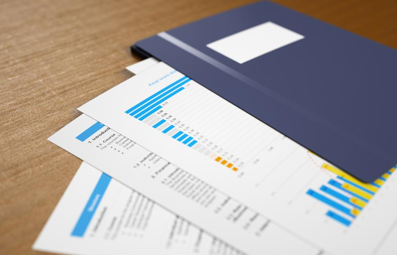 Printouts featuring reports and bar graphs are arranged on a table fanning out from a blue folder.