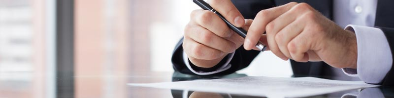 A businessman sits at a shiny table with a sheet of paper in front of him as he handles a pen.