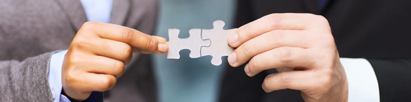 A businesswoman and businessman each hold one of two puzzle pieces that are joined at the centre.