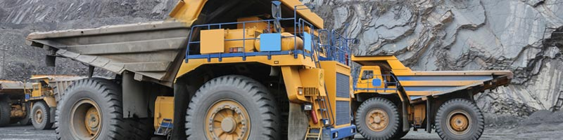 Four large, heavy-duty dump trucks can be seen at the site of an open pit mine.