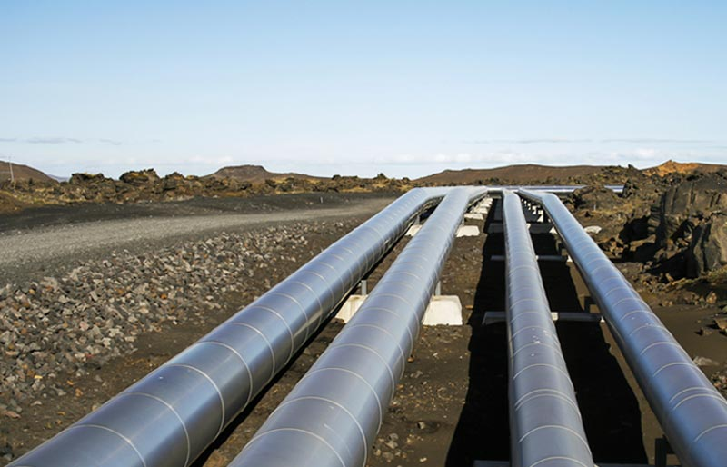 A perspective shot of four industrial pipelines that shows them stretching out into the distance.