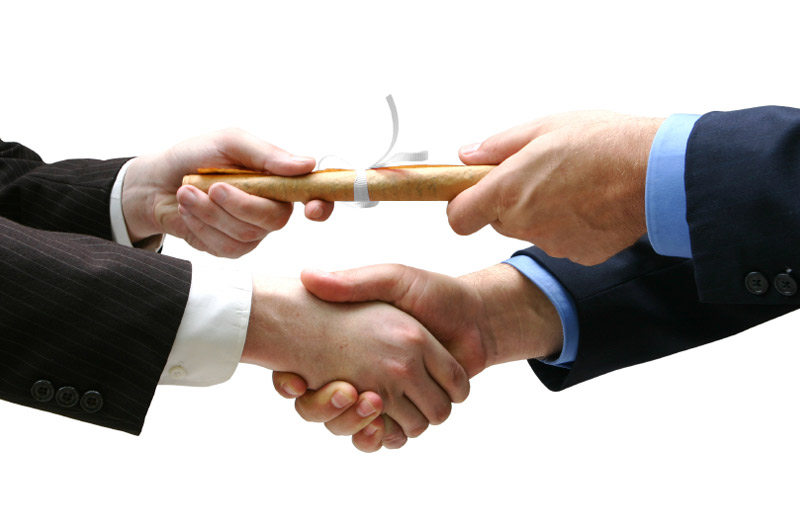 Close-up of a young man's hand shaking an older man's hand, above which they are each holding one end of a rolled up certificate or diploma.