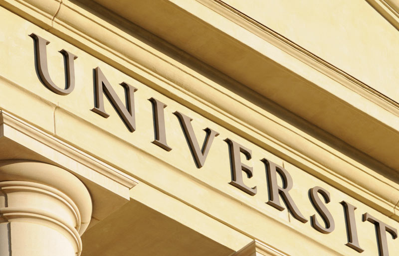 "Close-up of the word ""university"" as it is written on the front of a stately-looking building."