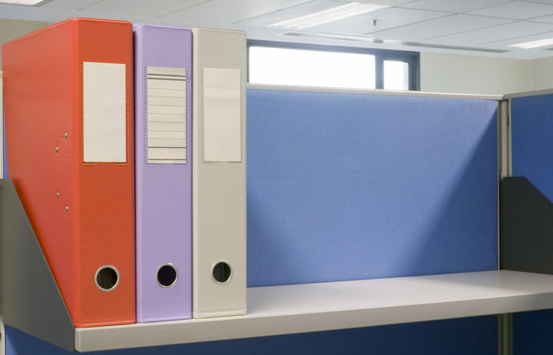 Three large binders sit neatly on a shelf in an otherwise bare office cubicle.