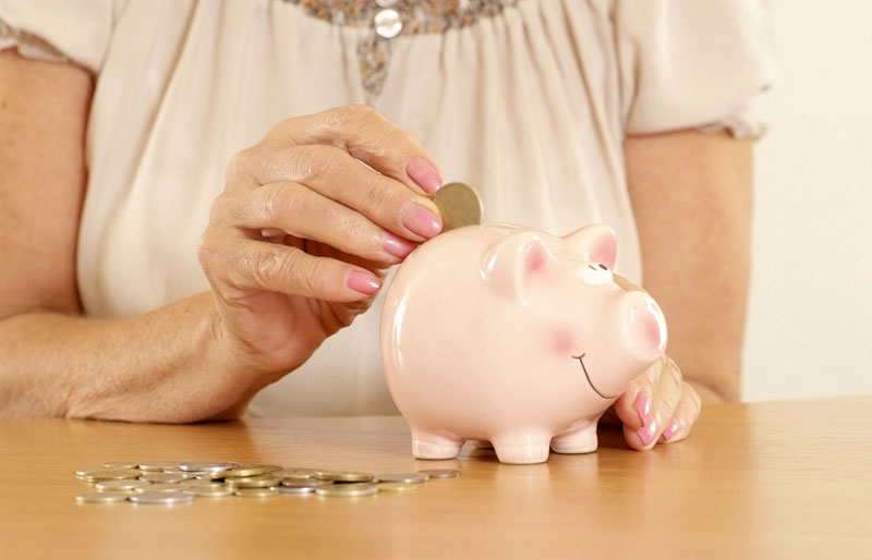 An older woman seated at a table puts a coin into a piggy bank.