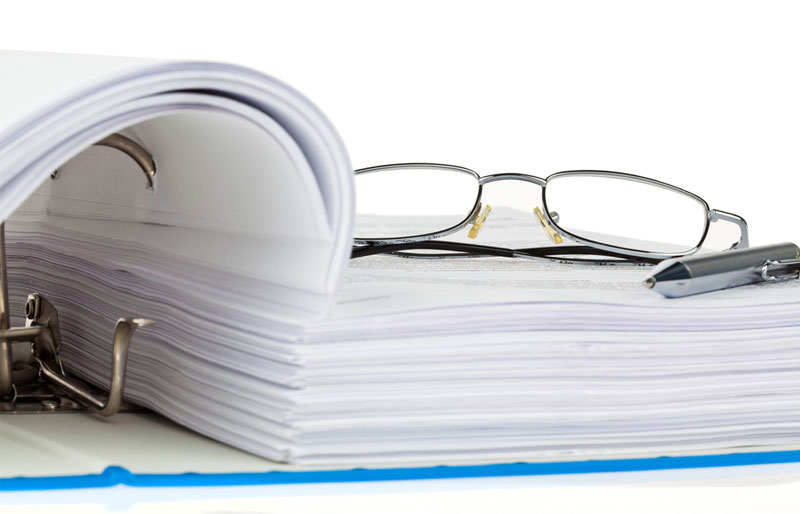A pair of glasses and a pen sit on an open page of a very large document in a loose-leaf binder.