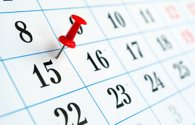 A red thumbtack is pressed into a calendar square indicating the fifteenth of the month.