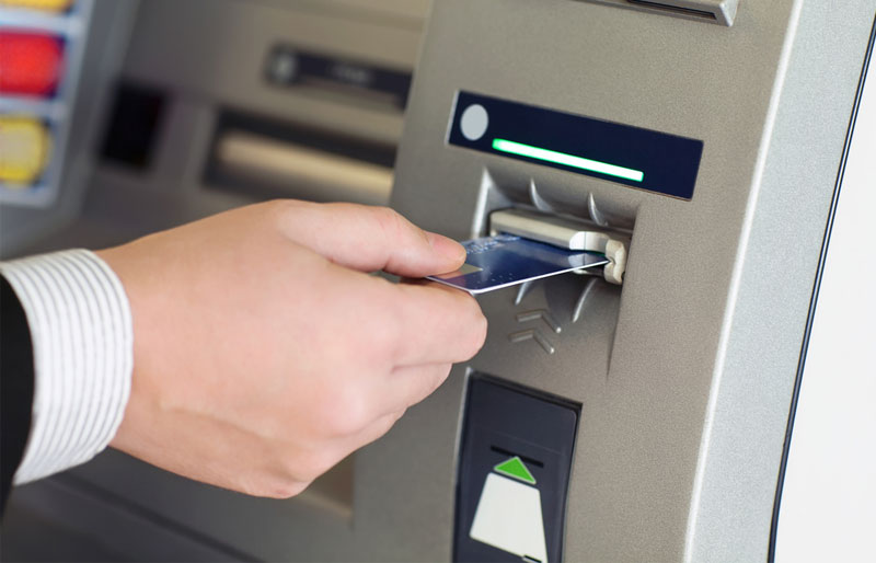A businessman puts a bankcard into an automated banking machine.