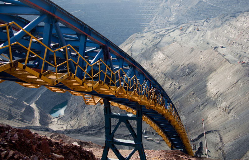 An ore conveyor stretches down into an open pit mining operation.